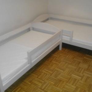 dwa białe łóżka dziecięce